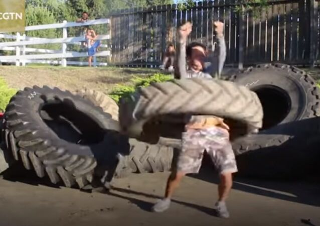 Man hola hoops with a 120 pound tractor tire