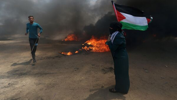 A woman holds a Palestinian flag as a demonstrator runs during a protest against U.S. embassy move to Jerusalem and ahead of the 70th anniversary of Nakba, at the Israel-Gaza border in the southern Gaza Strip May 14, 2018. - Sputnik France