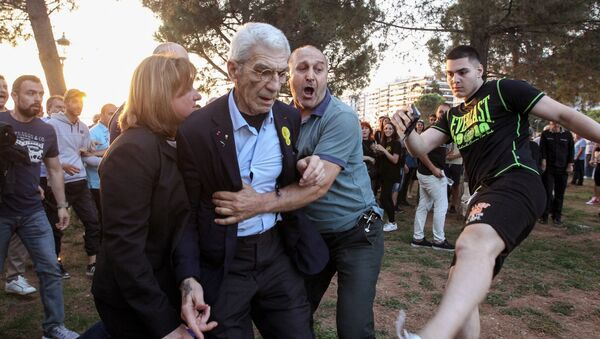 The mayor of Greece's second city, Thessaloniki, Yiannis Boutaris (C) is helped as he is assulted by suspected far-right members at a rally in Thessaloniki on May 19, 2018. - Sputnik France