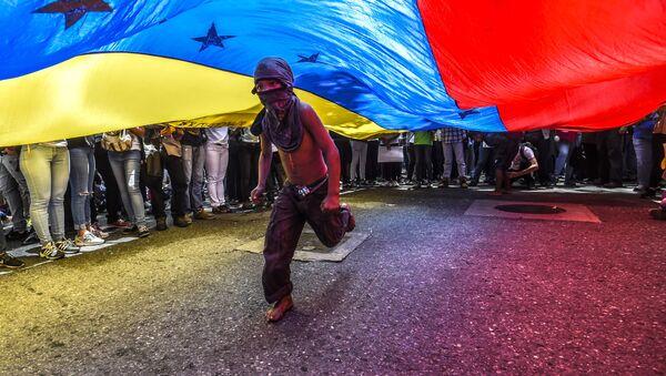 Мальчик бежит под венесуэльским флагом во время протеста журналистов и работников средств массовой информации против нападений на журналистов в Каракасе - Sputnik France