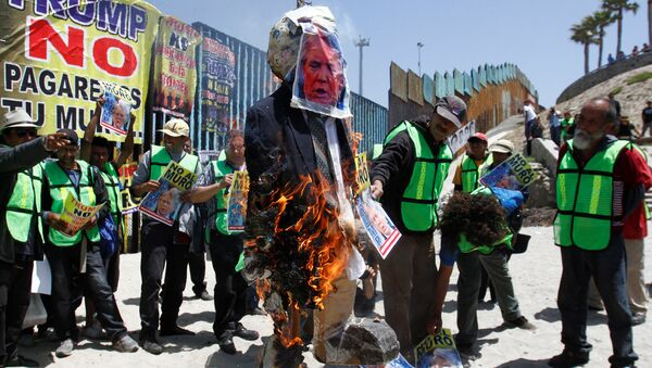 Demonstrators burn an effigy depicting U.S. President Donald Trump during a protest against the immigration policies of Trump's government near the border fence between Mexico and the U.S., in Tijuana, Mexico May 10, 2018 - Sputnik France