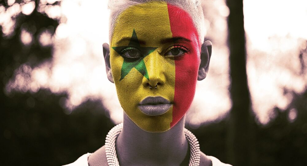 Une femme avec le drapeau sénégalais dessiné sur le visage