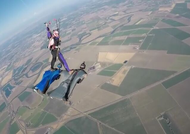 Un parachutiste se pose sur deux pilotes de wingsuit dans les airs