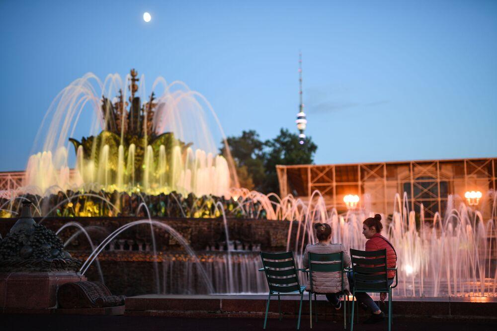 Des jeunes femmes devant la fontaine Fleur de pierre au VDNKh de Moscou.