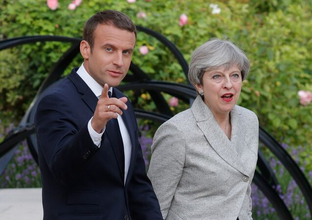 French President Emmanuel Macron (L) escorts Britain's Prime Minister Theresa May as they arrive to speak to the press at the Elysee Palace in Paris, France, June 13, 2017