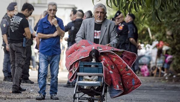A man carries his belongings and his dog as he leaves a Gypsy camp to be evacuated and demolished in Rome, Thursday, Sept. 9, 2010. - Sputnik France
