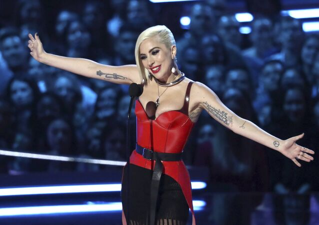 In this Saturday, June 16, 2018, photo, Lady Gaga presents the award for best movie at the MTV Movie and TV Awards at the Barker Hangar in Santa Monica, Calif