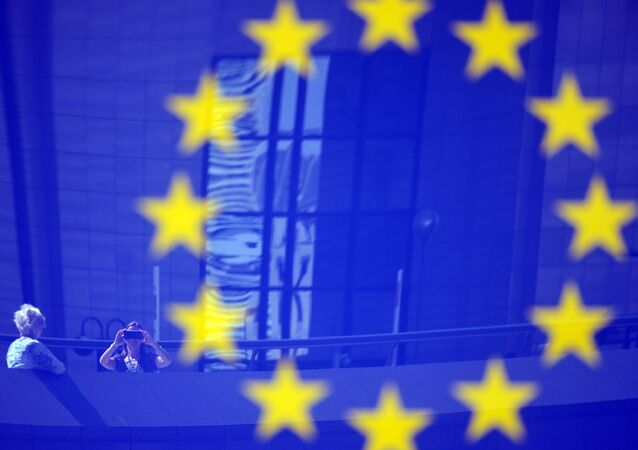 Tourists reflected in a EU logo