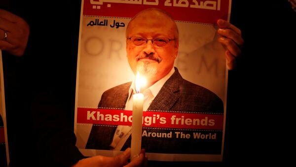 A demonstrator holds a poster with a picture of Saudi journalist Jamal Khashoggi - Sputnik France