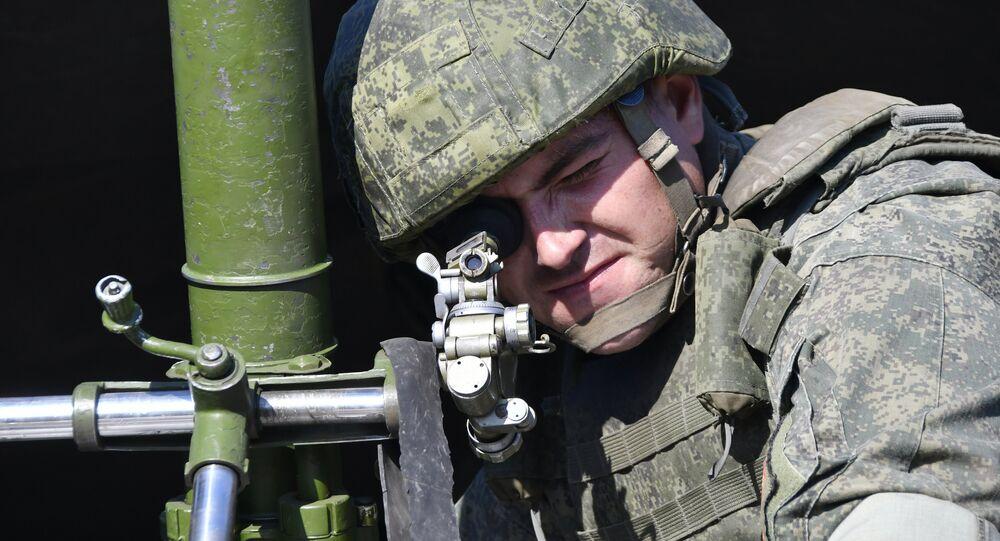 Un militaire russe tenant un mortier de 82 mm lors d'exercices