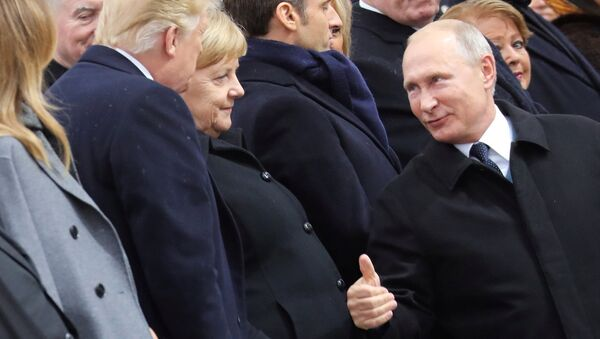 Russian President Vladimir Putin talks with German Chancellor Angela Merkel and U.S. President Donald Trump as they attend a commemoration ceremony for Armistice Day, 100 years after the end of the First World War at the Arc de Triomphe, in Paris, France, November 11, 2018. - Sputnik France