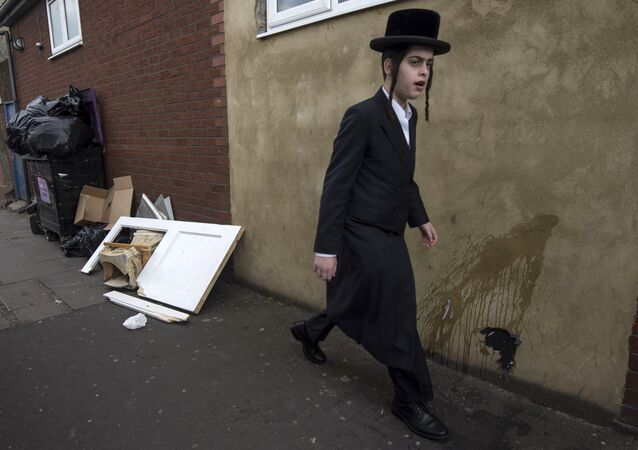 An Orthodox jew walks past a damaged door belonging to the Ahavas Torah synagogue in the Stamford Hill area of north London on March 22, 2015