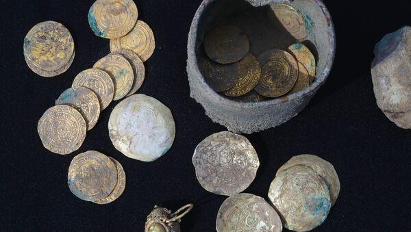 Un pot contenant 24 pièces d'or et des boucles d'oreille du même métal retrouvé lors de fouilles dans un quartier ancien de la ville israélienne de Césarée - Sputnik France