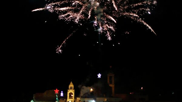 Christian Palestinians launch fireworks to celebrate the lighting of a Christmas tree at Manger Square, outside the Church of the Nativity in the West Bank town of Bethlehem - Sputnik France