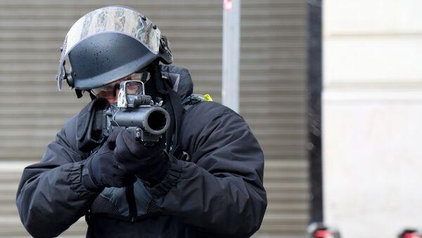 Un policier avec un LBD sur les Champs-Élysées - Sputnik France