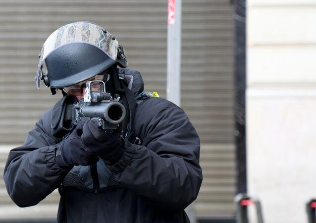 Un policier avec un LBD sur les Champs-Élysées