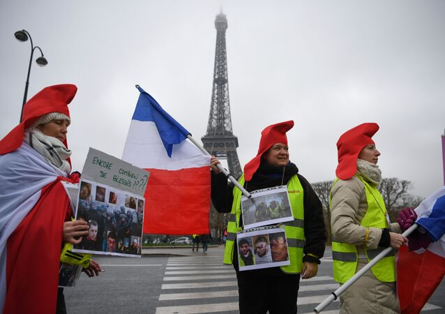 Women wearing yellow vests (gilets jaunes) hold pictures of protesters wounded by police forces in front of the Eiffel tower and a placard reading how many more wounded people?, in Paris, on January 20, 2019