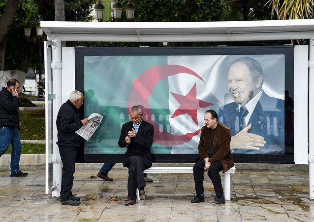 Des Algériens à un arrêt de bus sur lequel est accroché le portrait du Président Bouteflika sur fond du drapeau national algérien