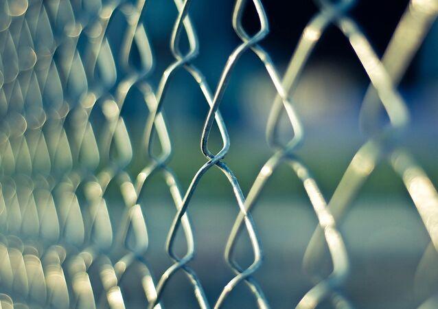 Un grillage à l'extérieur d'une prison