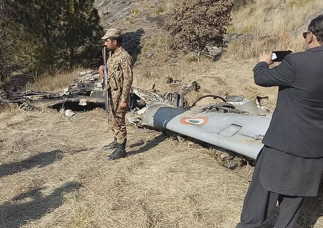 A Pakistani soldier stands guard near the wreckage of an Indian plane shot down by the Pakistan military on Wednesday, in Hurran, near the Line of Control in Pakistani Kashmir, Thursday, Feb. 28, 2019.