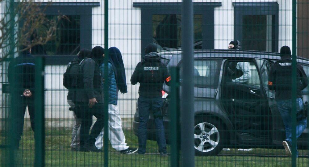 Des policiers conduisent une personne menottée au centre pénitentiaire de Condé-sur-Sarthe