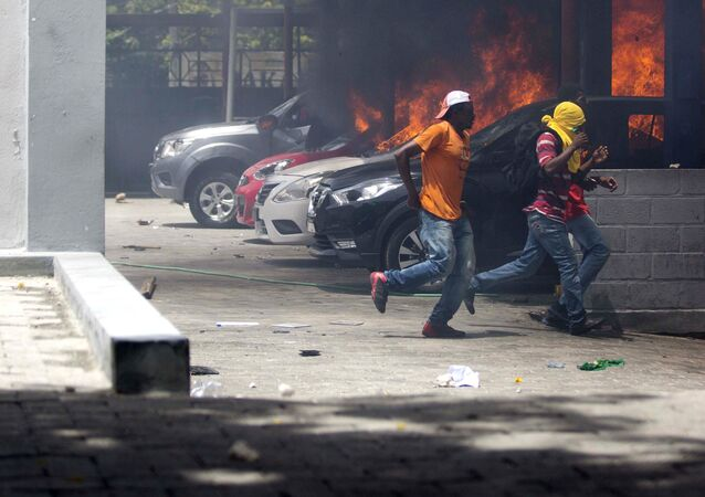 People run away after cars were set on fire at a Nissan dealership during protests over a fuel price increase in Port-au-Prince, Haiti, on Saturday, July 7, 2018