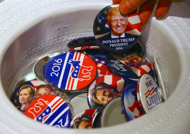 A guest at an event called the U.S. Presidential Election Watch, organised by the U.S. Consulate, reaches for a badge from out of a hat displaying photographs of Republican candidate Donald Trump and Democratic candidate Hillary Clinton, in Sydney, Australia