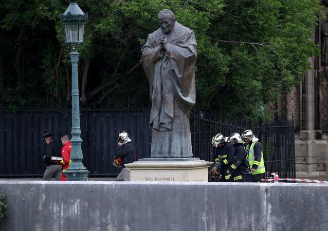 des sapeurs-pompiers près de la sculpture de Jean-Paul II après de l'incendie à Notre Dama de Paris