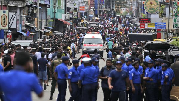 Sri Lankan police officers clear the road as an ambulance drives through carrying injured of Church blasts in Colombo, Sri Lanka, Sunday, April 21, 2019. A Sri Lanka hospital spokesman says several blasts on Easter Sunday have killed dozens of people. - Sputnik France