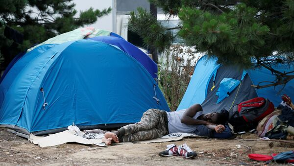 A migrant sleeps next to tents installed in a street near the entrance of the reception center for migrants and refugees at porte de La Chapelle, north of Paris, France, July 6, 2017 - Sputnik France