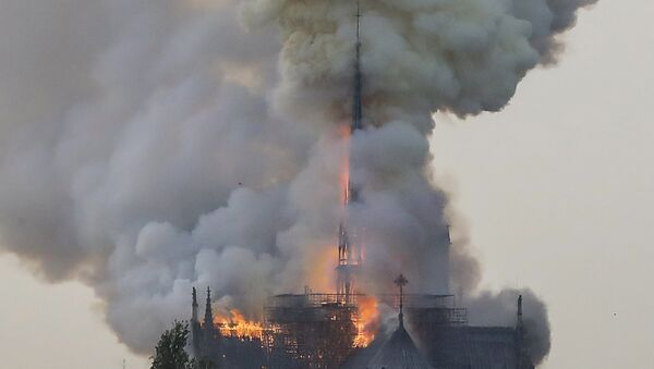 Flames and smoke are seen billowing from the roof at Notre-Dame Cathedral in Paris on April 15, 2019. A fire broke out at the landmark Notre-Dame Cathedral in central Paris, potentially involving renovation works being carried out at the site, the fire service said. - Sputnik France