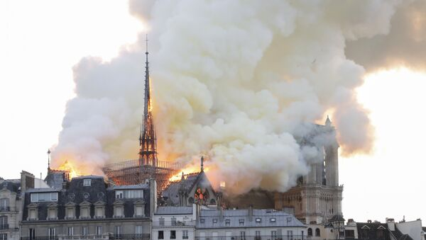 Smoke and flames rise during a fire at the landmark Notre-Dame Cathedral in central Paris on April 15, 2019, potentially involving renovation works being carried out at the site, the fire service said. - Sputnik France