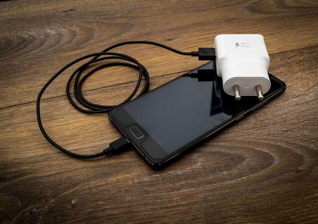 Un portable avec un chargeur (image d'illustration)