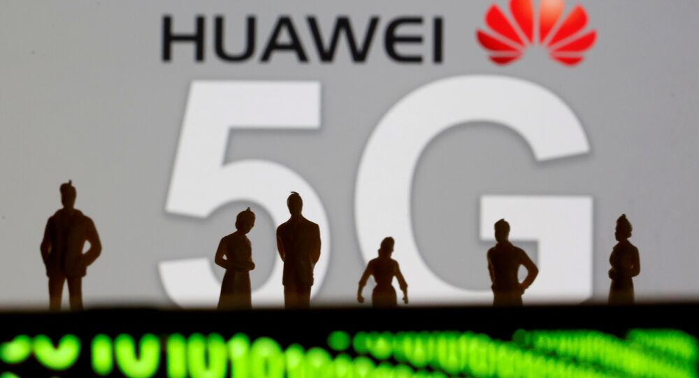 Small toy figures are seen in front of a displayed Huawei and 5G network logo in this illustration picture, March 30, 2019