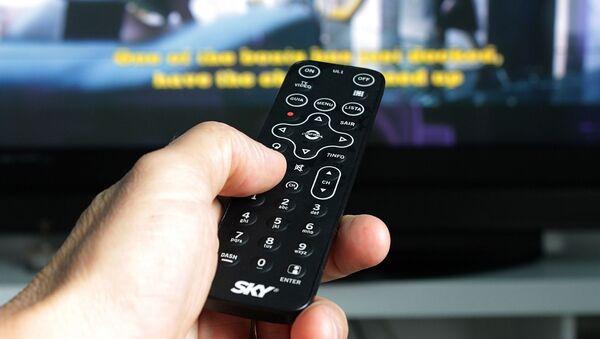 Рука с пультом напротив телевизора - Sputnik France