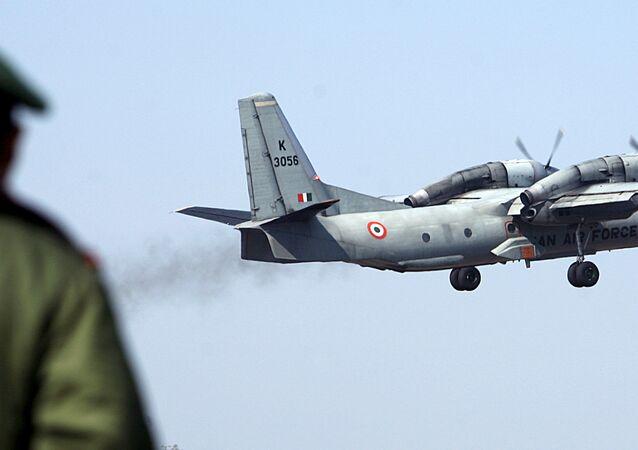 A soldier stands guard as an Indian Air Force AN-32 transport aircraft.