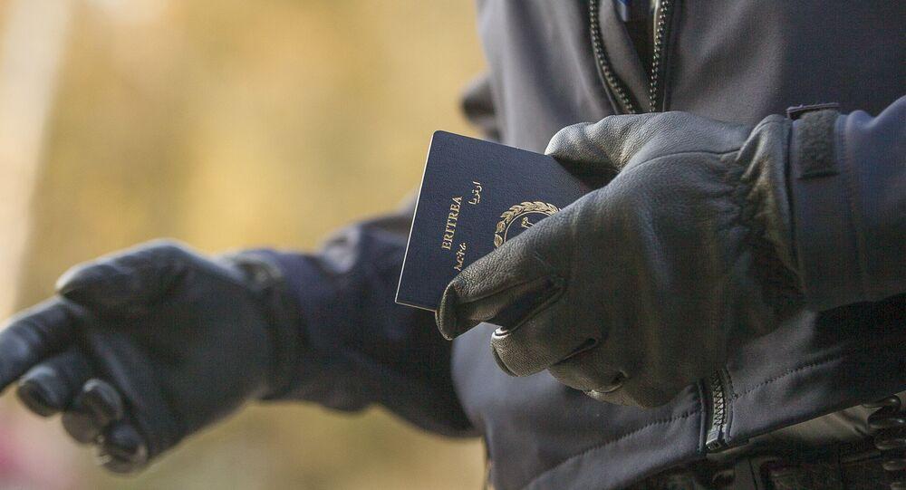 Un officier de la police aux frontières tient le passeport d'une femme érythréenne après son passage illégal de la frontière américano-canadienne