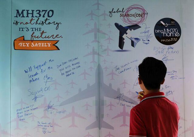 Un homme écrit un mot de condoléances lors de la journée de commémoration des victimes du MH370