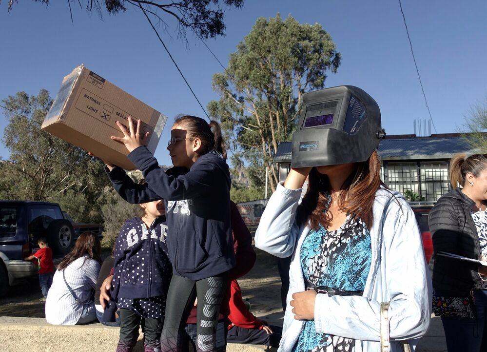 People test special glasses for viewing the total solar eclipse in La Paz, Bolivia, July 2, 2019