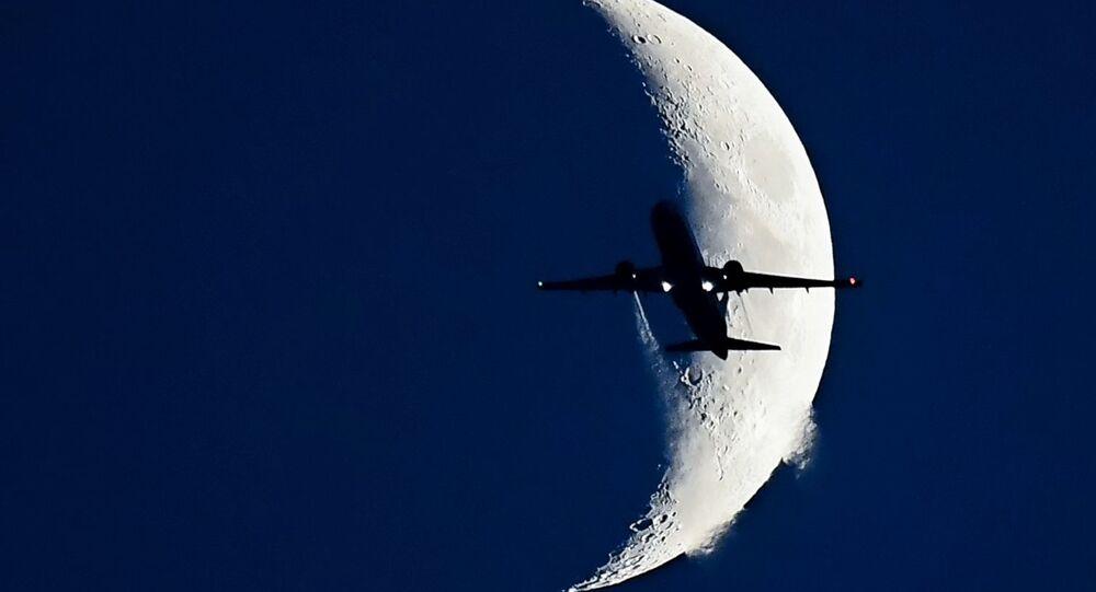 Самолет Boeing 737 на фоне растущей Луны.