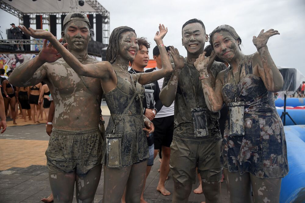 Tourists play in a mud pool during the 22th Boryeong Mud Festival at Daecheon beach in Boryeong on July 20, 2019. - The annual festival, which runs from July 19 to 28, aims to encourage the use of mud for cosmetic skin-care and to promote tourism in the region.