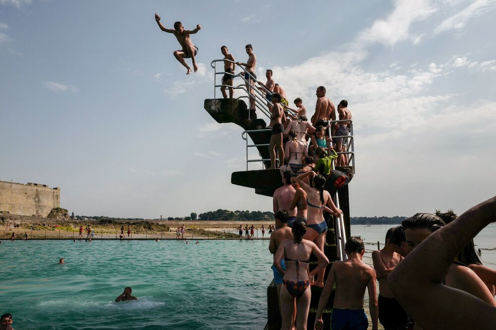 People queue to dive into the landmark sea pool of Saint-Malo, Brittany, on July 23, 2019 as a new heatwave blasted into northern Europe that could set records in several countries. - The new heatwave in northern Europe follows a three-day temperature peak from June 26-28 in France, which was four degrees Celsius (7.2 Farenheit) hotter than an equally rare June heatwave would have been in 1900, the World Weather Attribution (WWA) team said this month.