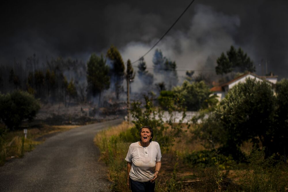 A villager shouts for help as a wildfire approaches a house at Casas da Ribeira village in Macao, central Portugal on July 21, 2019. - Planes and helicopters joined nearly 2,000 firefighters in central Portugal on July 21, 2019 to battle huge wildfires in a mountainous region where more than 100 people died in huge blazes in 2017. Around 20 people have been injured in the blaze, including eight firefighters and 12 civilians, according to the interior ministry.