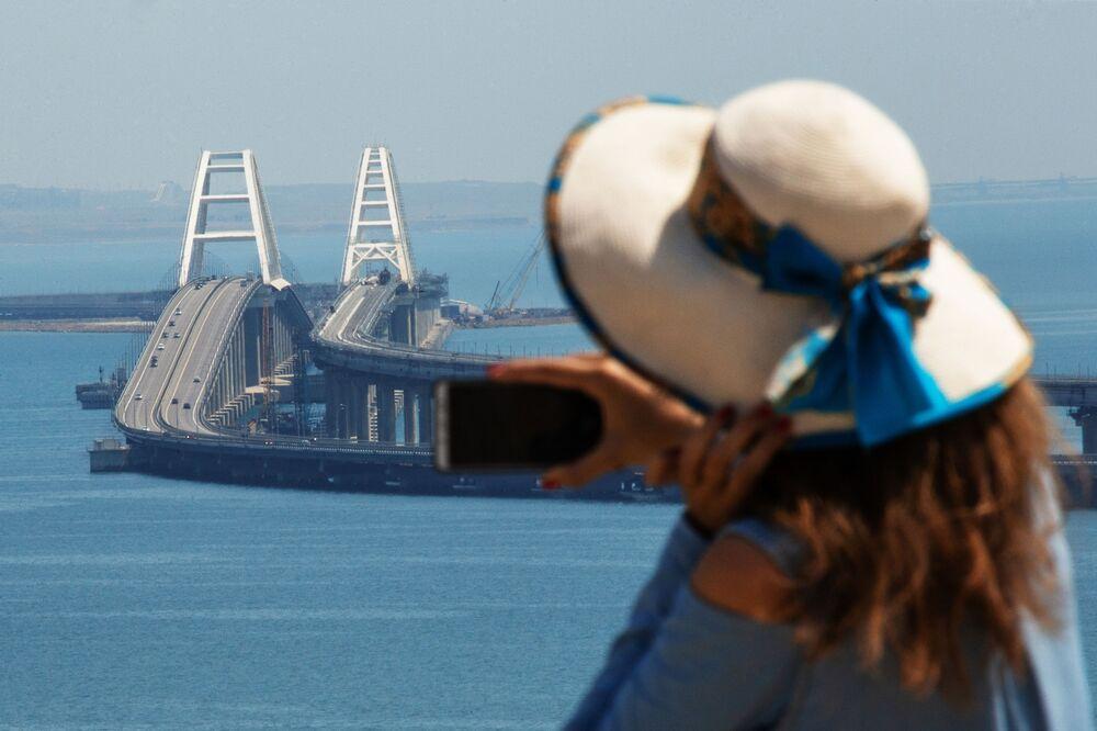 Девушка фотографирует Крымский мост через Керченский пролив.