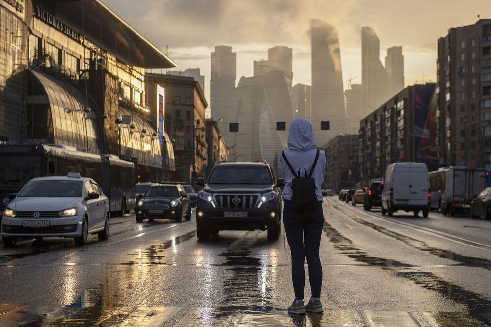 Девушка на пешеходном переходе на Кутузовском проспекте. На дальнем плане - небоскребы делового центра Москва-сити.