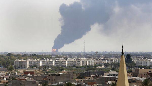 Une fumée noire jaillit sur l'horizon alors qu'un incendie au dépôt pétrolier de l'aéroport déchaînait après avoir été touché par des tirs croisés entre des milices belligérantes se battant pour le contrôle de l'aérodrome de Tripoli. - Sputnik France