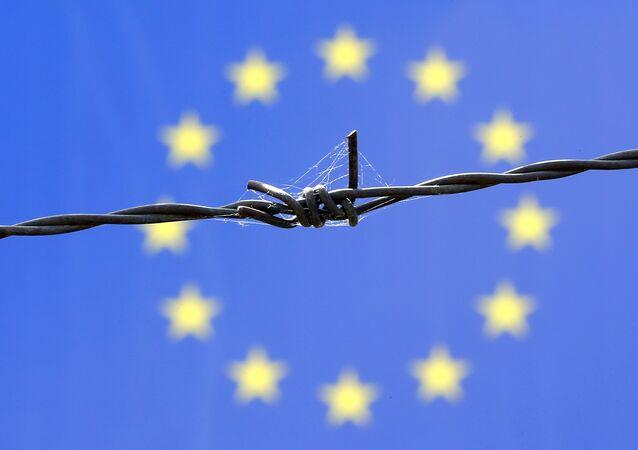 Fil de fer barbelé devant le drapeau de l'Union européenne