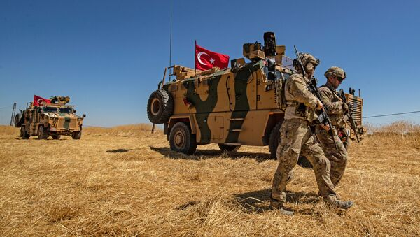 (FILES) In this file photo taken on September 08, 2019 US troops walk past a Turkish military vehicle during a joint patrol with Turkish troops in the Syrian village of al-Hashisha on the outskirts of Tal Abyad town along the border with Turkish troops - Sputnik France