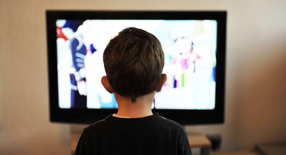 un garçon devant la télé