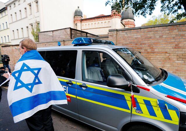 Un homme portant un drapeau israélien à côté d'un véhicule de police près de la synagogue de Halle